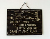 """Vintage """"The Best Way to Fight a Woman is With Your Hat... Grab it and Run"""" Wall Hanging"""