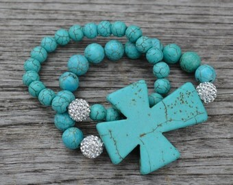 Blue turquoise gemstone beaded stretch bracelet accented with pave crystal beads and a large turquoise cross.