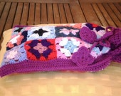 Granny square hot water bottle cover with corded flower motif fastener.