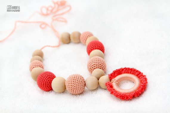 Teething necklace with wooden ring pendant in pastel peach and coral. Nursing/breasfeeding mom accessory