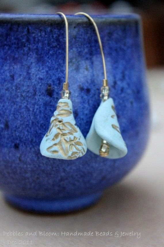 Bell shaped light-blue earrings with golden plant imprint