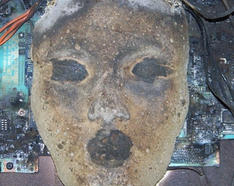 Burned concrete face sculpture with wiry hair wall art