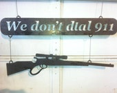 We Don't Dial 911 sign with rifle
