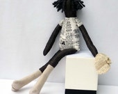 Fabric Doll with newspaper print dress and knitted corsage cap