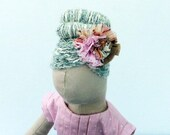 Fabric doll in peaches and cream.  She wears a pleat front dress with satin tie belt.