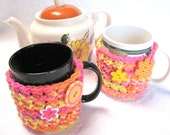 Matching pair of Bright Yellow/Orange Mug Hug cozies with coaster bottom, crocheted in 100% cotton, decorative buttons