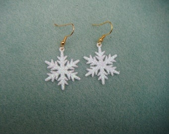 plastic white glittered snowflake earrings