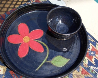 Stoneware chip/dip plate with attached bowl in deep blue with carved red daisy