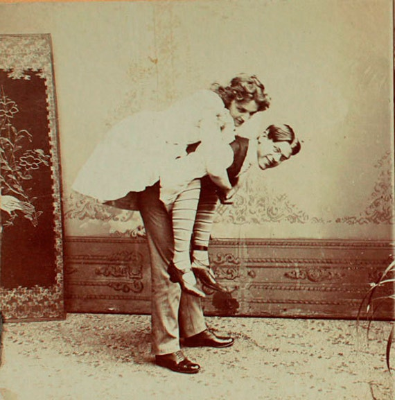 Antique stereowiew. Man carries a woman a piggyback ride. C. 1910