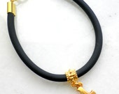 Beautiful Black Rubber Bracelet with gold plated puzzle charm and gold plated details