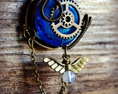 Steampunk Pendant: Antique Bronze w/Large Blue Glass, Gears, Cog, Wire Wrapping, Angel Wings and Ornate Key, Long Chain, Toggle