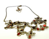 Delightful necklace made with red and black czech glass beads and irregular antique brass shapes