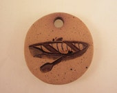 Small Handmade Clay Pottery Pendant Charm or Ornament - Round - Unglazed Background - Canoe
