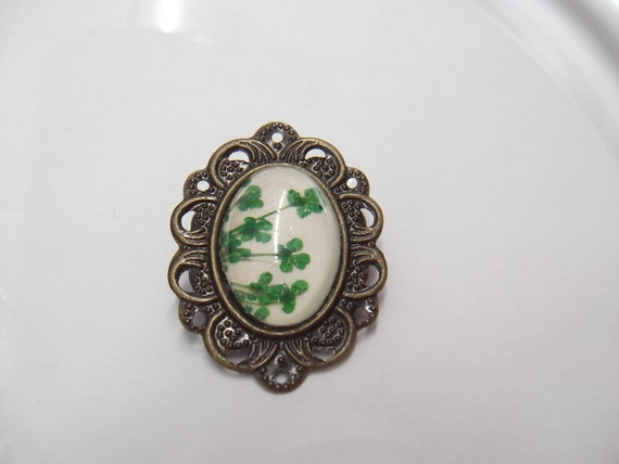 antiqued brass small brooch with green presses flowers and glass cabochon
