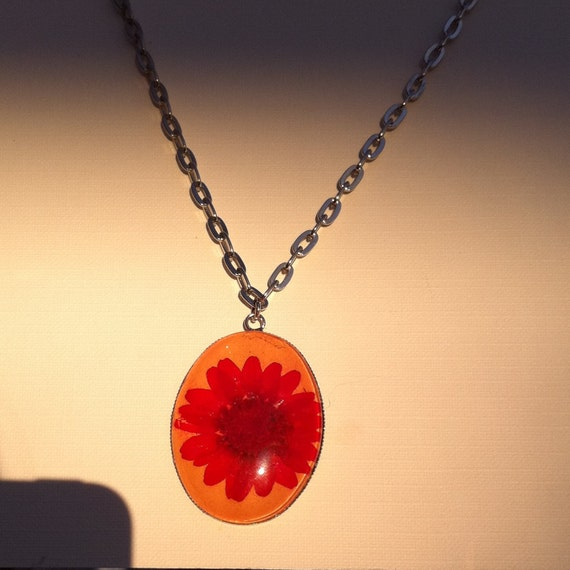 plated pendant with deep red pressed flower and a 30x40 mm glass cabochon