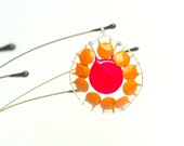 Daisy capacitor pendant made with upcycled light brown and red capacitors.