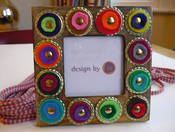 Square woden frame decorated with layered colorful felt rounded pieces, bottle tops and brass pins