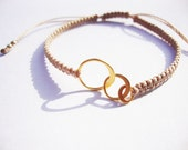 vermeil . macrame bracelet . charm bracelet . friendship bracelet . three interlocked vermeil rings with beige cord . adjustable