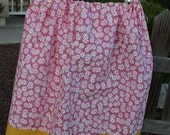 Womans pink with white daisy skirt and yellow hem