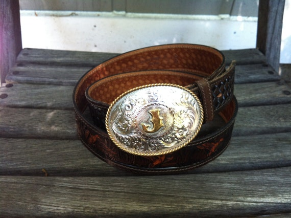 """Vintage """"J"""" Montana Silversmith silver plated belt buckle on a Western hand tooled leather belt"""