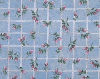 Pink rosebuds on white lattice over blue print fabric