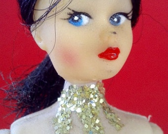 Glamorous Gold Showgirl Doll wearing glitter swimsuit and matching sparkling collar.