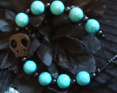 Turquoise and Black beaded bracelet on leather cord with black skull bead