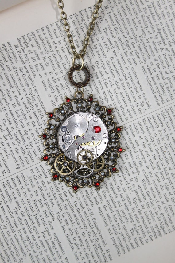 Steampunk watch movement and cogs set into an ornate frame with red rhinestone and pear detail