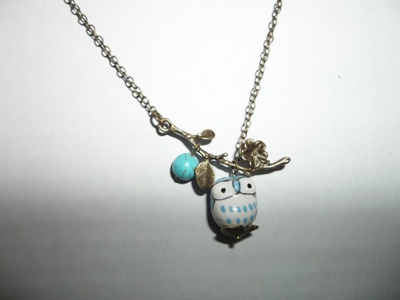 Ceramic blue owl with turquoise bead on a branch