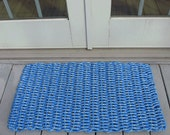 Brightly colored blue handwoven doormat from lobster trap rope.