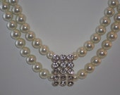 Beautiful pearl and Cubic zirconia brooch necklace that features a pretty silver clasp closure.