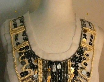 wood with metal and seed beads applique on white mesh
