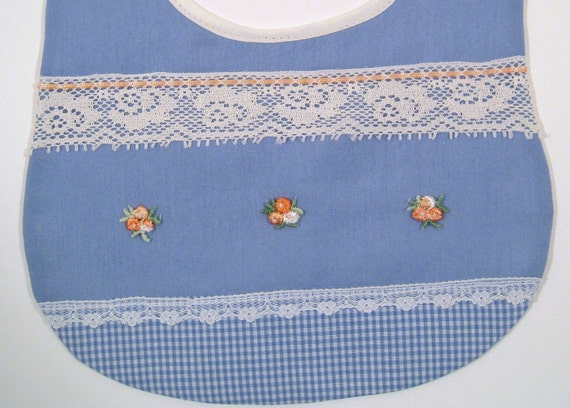 Baby bib in blue fabric, accented with 3 pretty peach flowers applique, ribbon, and lace.