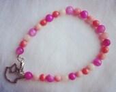 pink beaded bracelet with silver bird pendant