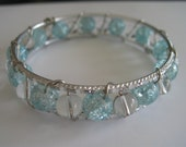 Wire wrapped silver bangle bracelet with light blue frosted and clear beads