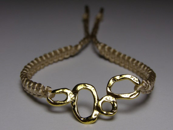 Tan/champagne colored bracelet with bubbly goldish finding