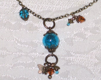 Asymmetrical antiqued brass and blue glass bead necklace
