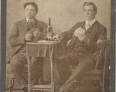 Two men playing cards with Schlitz beer on table Wm. H Beck Morrisville, Ill, photographer