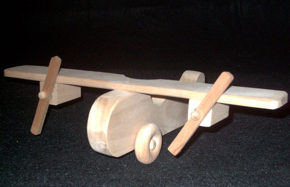 Wooden toy bomber type airplane with dual spinning propellers.