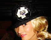 Fedora sparkly hat with a one of kind black and cream accent flower decorated with rhinestones.