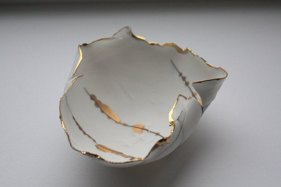Paper thin bowl made out of fine bone china looking like a curled leaf with 10% real gold.