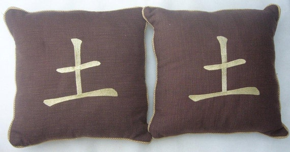 A pair of brown tactile cushions with the Chinese symbol for Earth on them in Gold