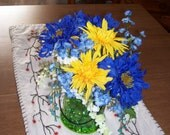 Bright as sunshine, this includes bright blue Gerber daisies, and a green vase