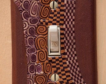 Checkerboard and spiral, purple and mauve and gold, polymer clay glow-in-the-dark switch plate cover