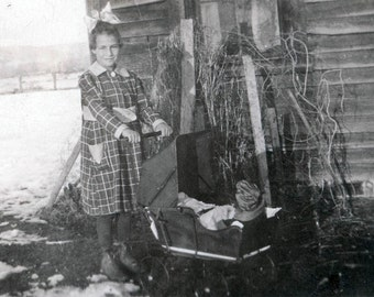 vintage photo little girl pushes her doll w stroller on the farm