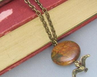 A brass bird, and cherry creek jasper necklace.