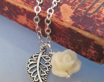 A single flower grows. A cream, white, resin rose, spring flower, and silver filigree leaf necklace.