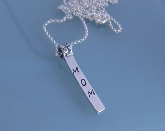 Sterling silver stamped vertical bar pendant. Custom word stamped to order