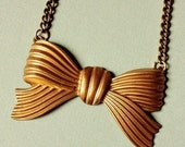 a vintage ribbed brass bow necklace .