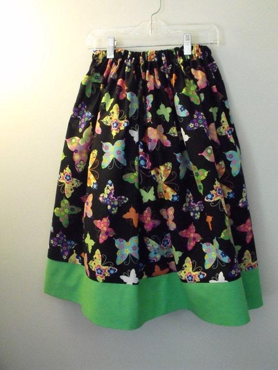 Girl's skirt, modest, multicolored butterflies on black background w/green band at hem